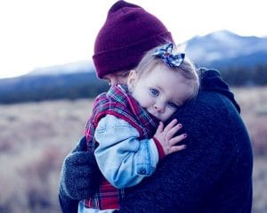 father holding his daughter in cold weather
